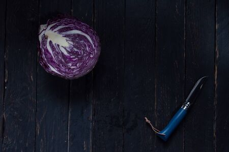 Sliced cabbage with a knife. Purple cabbage and a blue knife. Kitchen knife. Reklamní fotografie - 132195864