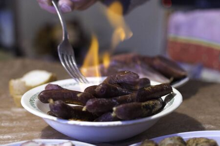 Sausages on fire. Sausages burning in a plate. Fork.