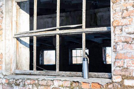 Iron bottle by the window. flask by the window on the ledge. Shiny flask. Reklamní fotografie