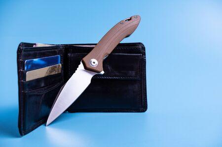 Knife, wallet and money. Knife and credit cards. Gently blue background. Reklamní fotografie