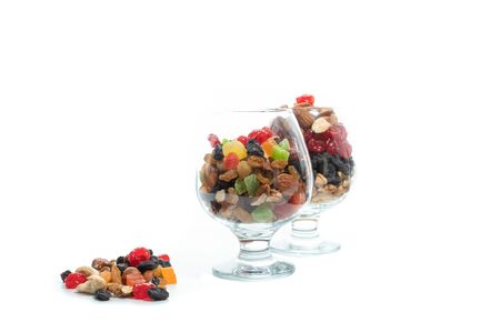 Two glasses with a variety of nuts and dried fruits. Colorful berries. A variety of nuts. Isolate Standard-Bild - 133168535