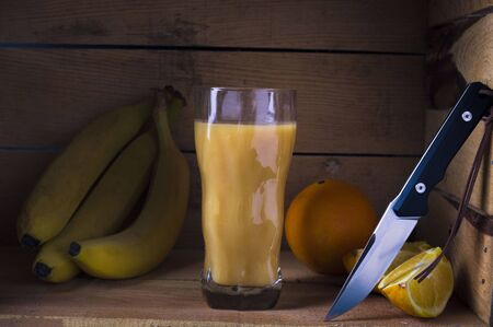 Multivitamin juice with fruits. Citrus juice. Juice from bananas and oranges. Knife and fruits.