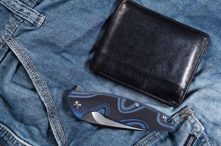 Folded knife. Knife and purse. Mens attributes. Top. Reklamní fotografie