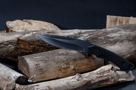 Large knife with a fixed blade. Knife on chopped wood. Front view. Reklamní fotografie