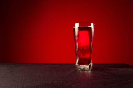 A glass of red drink. Glass of drink on a red background. Foreground.