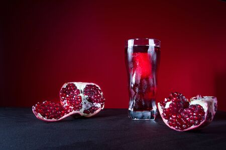 A glass of pomegranate juice. Freshly squeezed pomegranate juice. Drops on a glass. Condensate.