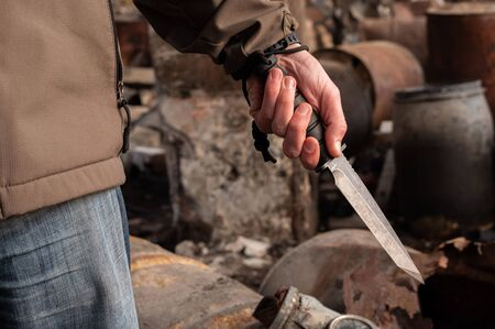 A man holds a knife in his hand. Big bayonet knife in the hand. Fron view. Reklamní fotografie