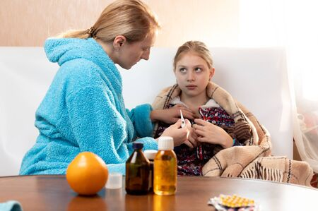A woman inserts a thermometer to a girl. Mom with a thermometer.Medicines.
