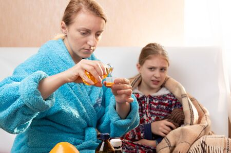 Mom pours cough syrup. Mom treats her daughter. Home treatment. Reklamní fotografie