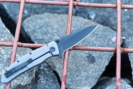 Knife with a clip to carry in your pocket. Pocket knife. Knife on the cage. Top.