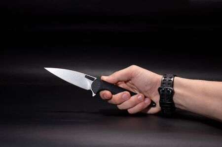 Knife in hand. Pocket knife in hand. Knife and clock on hand. Black background.