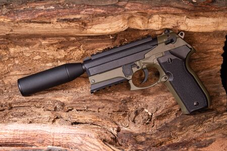 Khaki pistol with a silencer. Gun on a wooden background. Weapons.