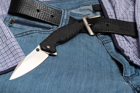 Men's casual style. Knife and jeans. Mens clothing. Blue jeans.