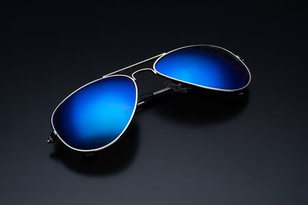 Sunglasses on black. Sunglasses with bright blue glasses. Top view at an angle. Stok Fotoğraf