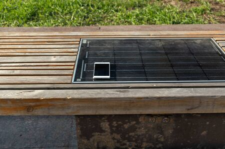 Solar charger mounted in a bench. City shop with a solar battery. Charge a smartphone from a bench. Banque d'images