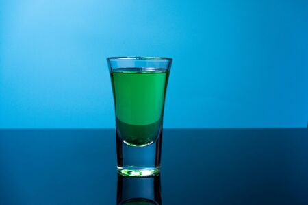 A glass of green drink. Glass of tequila on a blue background. Front view.