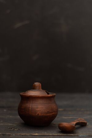 Clay pot with a lid and a clay spoon. Pottery on a black background. Vertical frame.