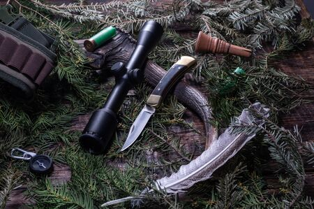 Hunting knife and optical sight against the background of needles. Hunting concept with a knife and a scope. Top.