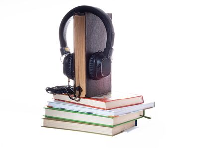 Listening to books through headphones. Listening to stories through books. Live book and headphones. Isolate.