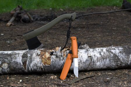 Set of huntsmen in the forest. Ax and knife in a birch log.