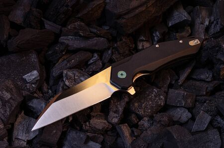 A sharp pocket knife lies at an angle on the coals. Top.