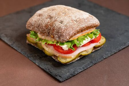 A sandwich on a tray. Sandwich with meat and vegetables on a black granite stand. Special square roll for sandwiches.