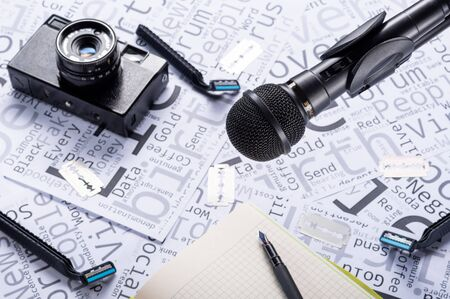 Journalistic concept. Abstraction with a microphone and a camera. Notebook for writing and pen.