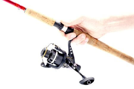 A fisherman holds a fishing rod with a reel. Spinning and reel. Fishing. Isolate. 스톡 콘텐츠