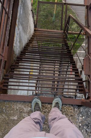 Descent along the iron stairs. Human feet on the edge of the stairs. View from above.