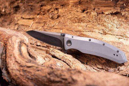 Folding knife with aluminum handle and black blade. Knife on a wooden texture. Hollow tree.