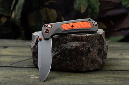 Very sharp knife with a khaki and orange handle. The knife is in a semi-folded position. Front view.