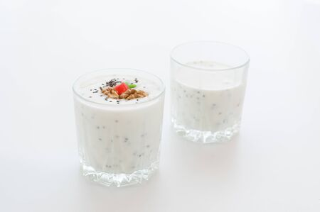 Two glasses with chia pudding. Milk dessert with chia seeds. High key.