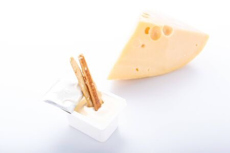 Bread sticks in a box with cheese sauce. Cheese sauce and hard cheese on a white plate. Front view.
