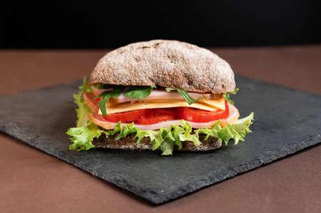 Sandwich on a slate board. Sandwich from the menu. Front view.