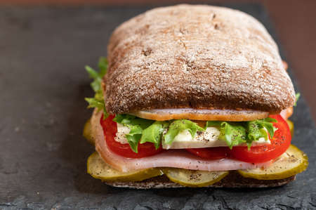 A sandwich with various fillings. Angled front view. Vegetables and meat.