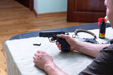 A man at home holds a gun in his hands. A man with a pistol. Stock Photo