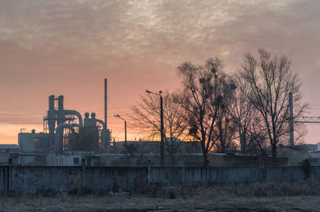 Morning glow over the plant. Fiery sky over the factory. Morning fog at the old factory. Plant and trees. 写真素材