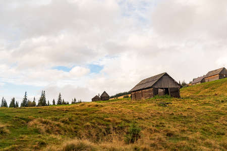 Old wooden houses in the highlands. Bottom view of the houses. Clouds over houses in the mountains. Village.