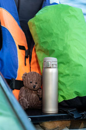 Children's flask and children's toy bear. flask for hot drinks. Vertical frame.