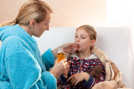 The sick child is taking medication. A child with a cold is taking medicine.
