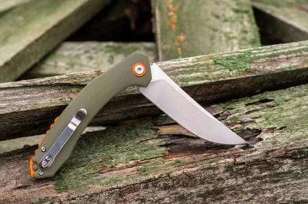 Knife with a green handle on green wooden sticks. Clip-on handle.