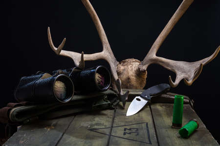 Hunting scene with objects and antlers. Bandolier and cartridges. Front view.