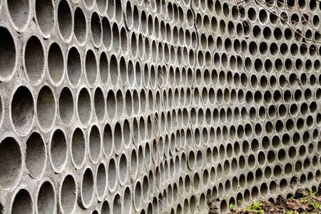 Pattern with many repetitions. Background and texture. Many holes in a concrete fence.