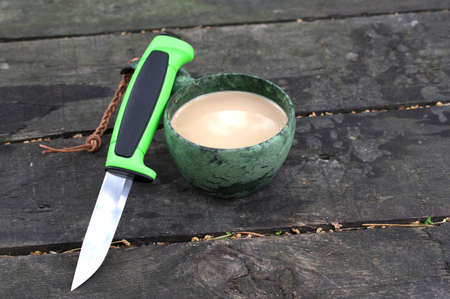 Knife with a green handle and a green mug. Wooden background. View from above.