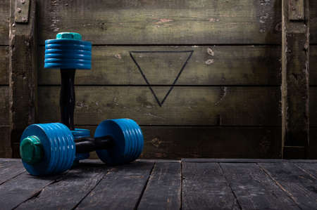 Athletics dumbbells against the background of a military box. Dumbbells and free space.