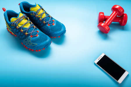 Blue running shoes on a blue background. Blue sneakers and red dumbbells. Angle view.