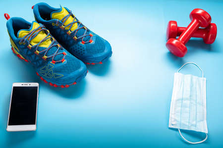 Sports sneakers, smartphone and medical mask on a blue background. Compulsory things in the gym. Angle view.