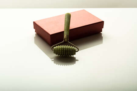 Facial massage roller. Roller made of stone. Massage roller and packaging.