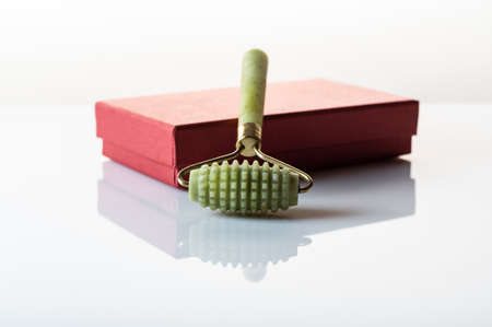 Jade stone roller for a rough facial massage. Massager for face and body.