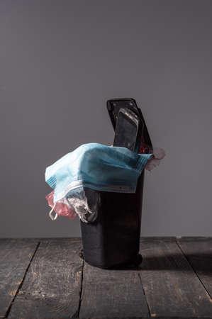 Medical mask in the trash can. A worn-out medical mask. Vertical frame.
